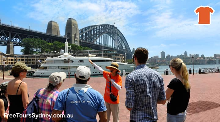 Sydney Free walking tour is at Campbells Cove. Local tour guide in an orange 'Free Tours' T-shirt is uncovering the history of the Rocks. The Sydney Harbour Bridge is in the background of the picture.