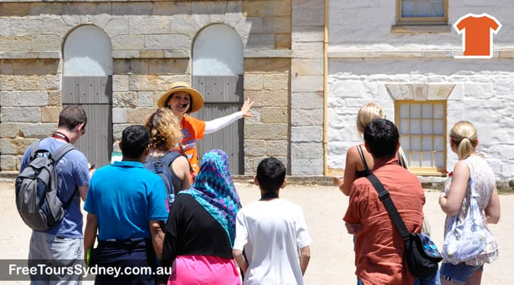 Travellers who joined a free walking tour around Sydney are at the Rocks area of Sydney. A tour guide in an orange 'Free Tours' uniform tells local stories of an early colony near one of the oldest surviving buildings in Sydney - Cadmans Cottage.