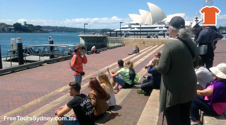Free walking tour Sydney. A group of travellers is enjoying the view of Sydney Harbour with the Sydney Opera House in the background. A tour guide in an orange 'free tours' uniform is telling stories of early Sydney.