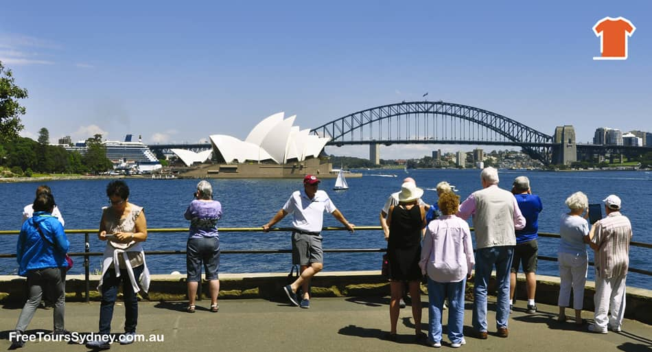 Sydney sightseeing bus tour stopped at Mrs.Macquaries Point. Travelers are taking pictures with the Sydney Opera House and Sydney Harbour Bridge at the background.